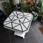 Up-cycled painted octagonal Art Deco side table 20″W x 20″D x 20.5″H applied geometric design under toughened glass top.